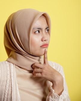 Close up donna hijab con un'espressione felice pensando a qualcosa di isolato su sfondo giallo