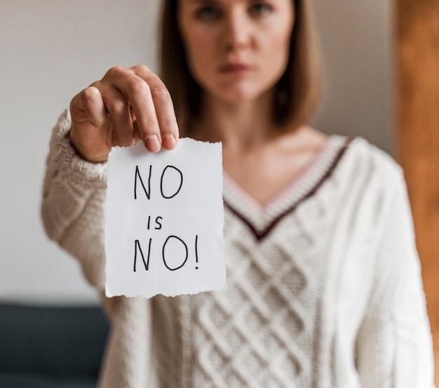 Primo piano di una donna che tiene un messaggio di consapevolezza