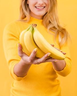 Banane della tenuta della donna del primo piano