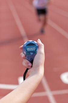 Primo piano di una donna che tiene un cronometro per misurare le prestazioni di un velocista