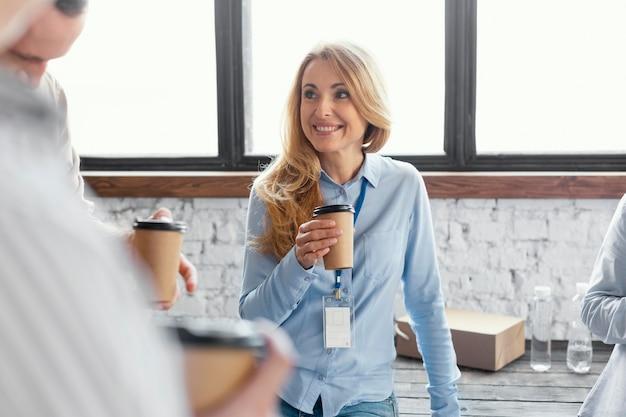 Chiuda sulla tazza di caffè della tenuta della donna