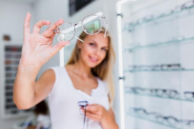 Primo piano del telaio degli occhiali della tenuta della donna