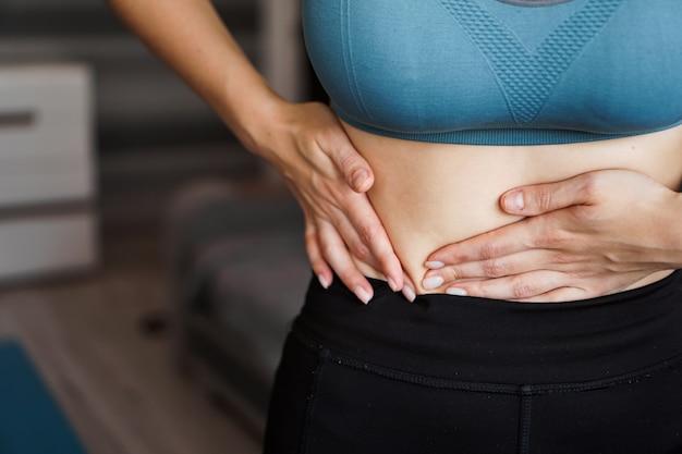 Primo piano della donna che tiene la sua pancia. dolore dopo l'allenamento a casa. perdita di peso, corpo snello, concetto sano