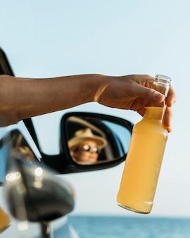 Donna del primo piano che tiene la bottiglia del succo fuori dal finestrino dell'auto