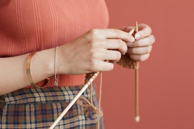 Primo piano della donna che tiene i ferri da maglia che lavora a maglia per se stessa in piedi contro il muro rosa