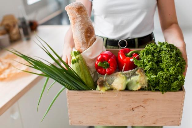 Donna del primo piano che tiene i generi alimentari organici