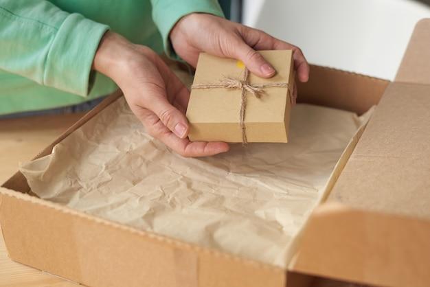 Primo piano della donna che tiene piccola scatola imballata mentre apre il suo pacco