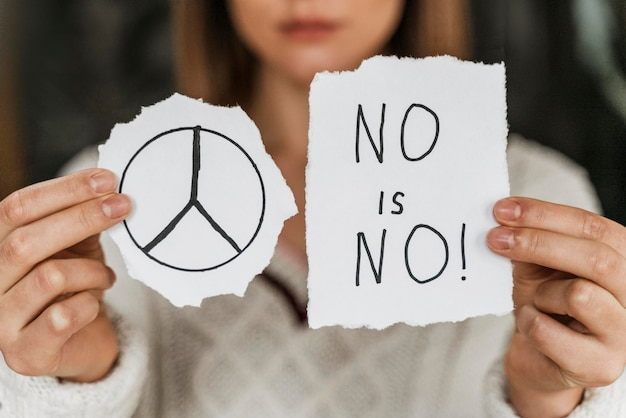 Primo piano di una donna che tiene un segno di pace