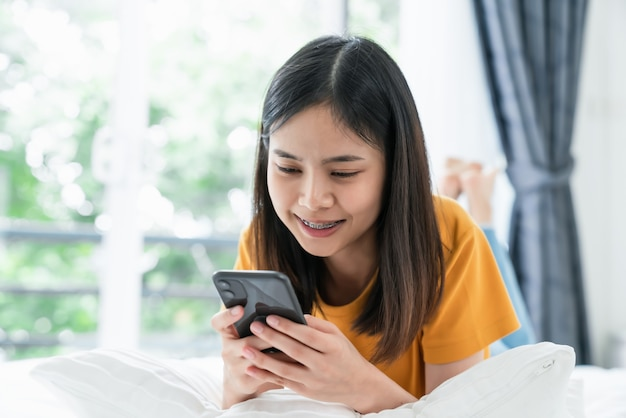 Primo piano della donna che tiene uno smartphone e utilizzando social online sullo stile di vita. tecnologia per il concetto di comunicazione.