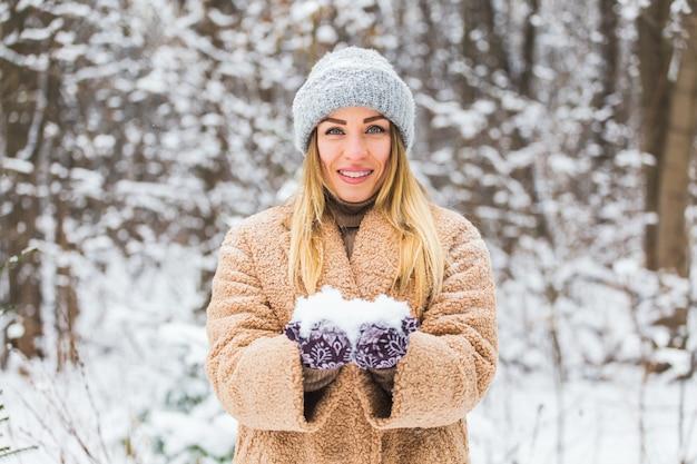Chiuda in su della donna che tiene la palla di neve nelle mani, concetto di inverno con lo spazio della copia