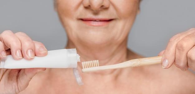 Donna del primo piano che tiene spazzolino da denti e dentifricio