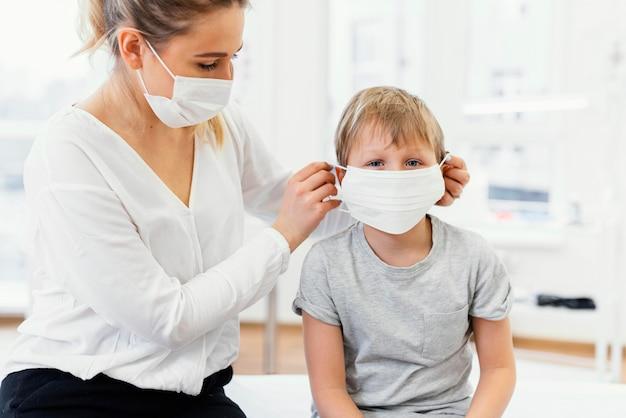Close-up donna e bambino che indossa la maschera