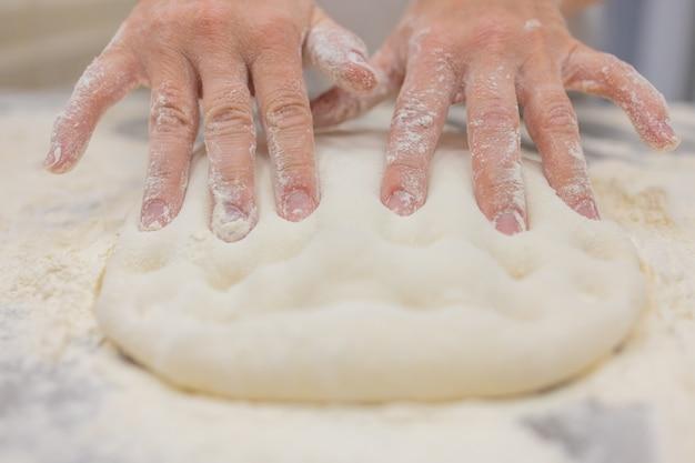Chiuda in su della donna che impasta la pasta per pizza.