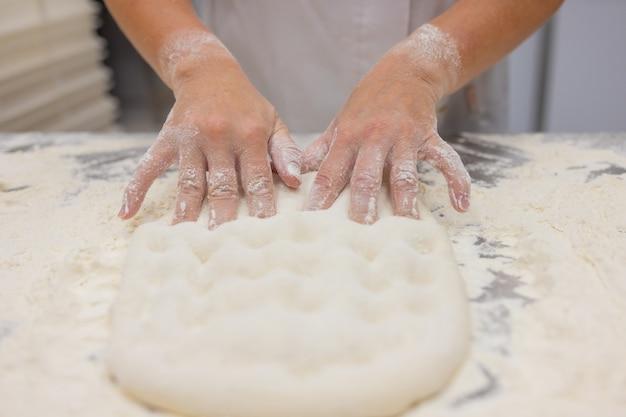 Chiuda in su della donna che impasta la pasta per pizza. Foto Premium