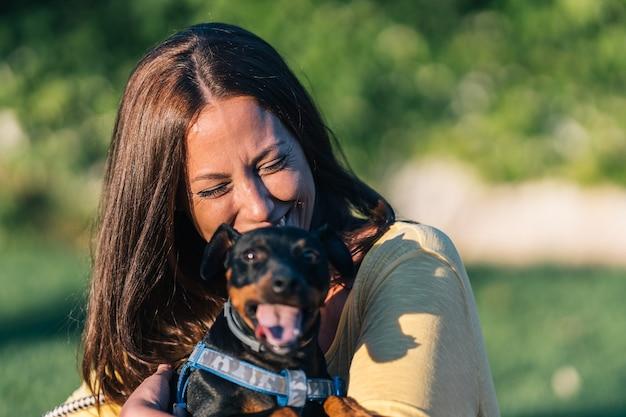 Primo piano di una donna che ride con il suo cucciolo nel parco. ridere giovane donna che abbraccia con il suo animale domestico.