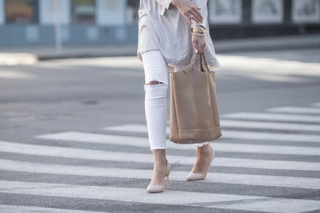 Stretta di gambe di donna che cammina su strisce pedonali. la donna indossa scarpe con i tacchi alti.