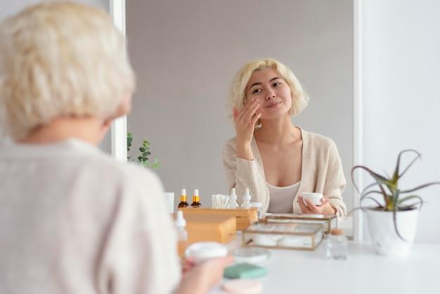 Chiuda sulla donna che osserva nello specchio