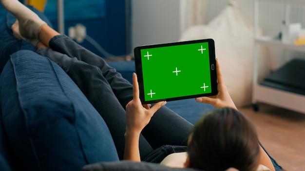 Chiuda in su della donna che guarda il computer tablet in modalità orizzontale con mock up display chroma key schermo verde sdraiato sul divano. libero professionista che utilizza un dispositivo touchscreen isolato per la navigazione sui social network