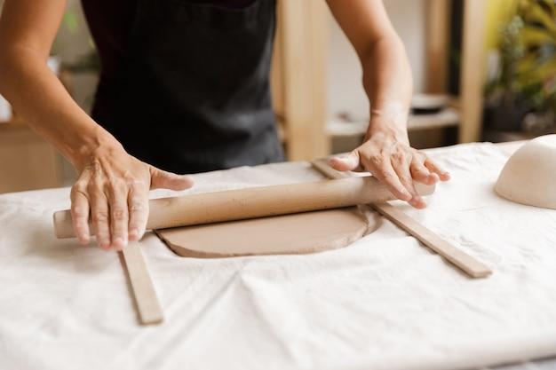Primo piano di una donna che fa ceramiche e stoviglie in ceramica in officina, lavorando con l'argilla