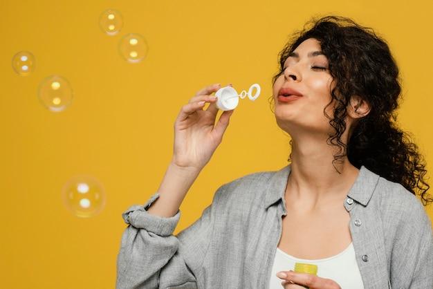 Donna del primo piano che fa le bolle di sapone