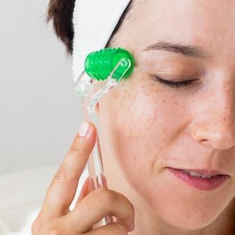 Donna del primo piano che massaggia la sua pelle del viso