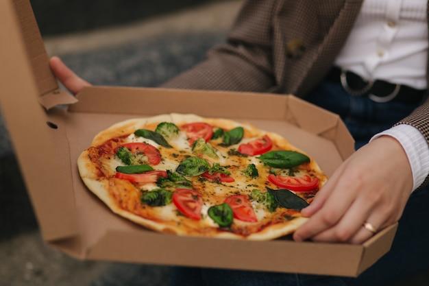 Chiuda in su della scatola della pizza aperta della donna all'aperto