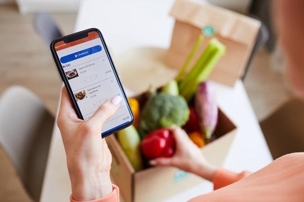 Primo piano della donna che ordina cibo online dal suo telefono cellulare a casa