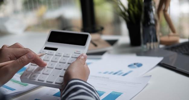 Close up donna pianificazione budget, utilizzando calcolatrice e laptop, lettura di documenti, giovane donna che controlla le finanze, conteggio bollette o tasse, servizi bancari online, seduto alla scrivania