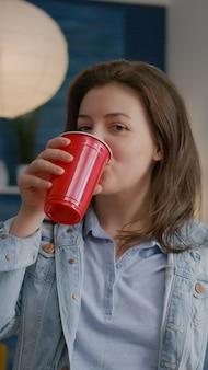 Primo piano di un ritratto di donna che guarda davanti mentre beve birra festeggiando