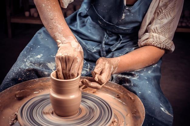 Primo piano una donna vasaia scolpisce magnificamente una ciotola profonda di argilla marrone e taglia l'argilla in eccesso su un tornio da vasaio in un bellissimo laboratorio