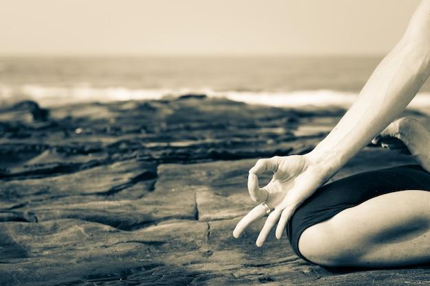 In prossimità di una donna a praticare yoga sulle rocce in riva al mare a goa, india. yogi sulla spiaggia. meditazione, consapevolezza, concetto di connessione con la natura