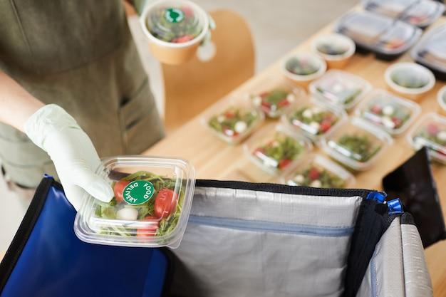 Primo piano della donna in guanti protettivi che imballano le scatole di verdure fresche nel sacchetto e che effettuano la consegna
