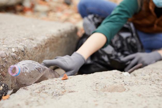 Primo piano della donna in guanti protettivi raccogliendo le bottiglie di plastica che pulisce la natura