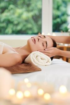 Primo piano della donna che si rilassa durante il massaggio termale nel salone della stazione termale