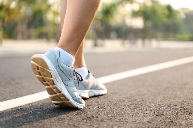 Chiuda su delle scarpe del corridore della donna nel parco. concetto di salute e fitness.