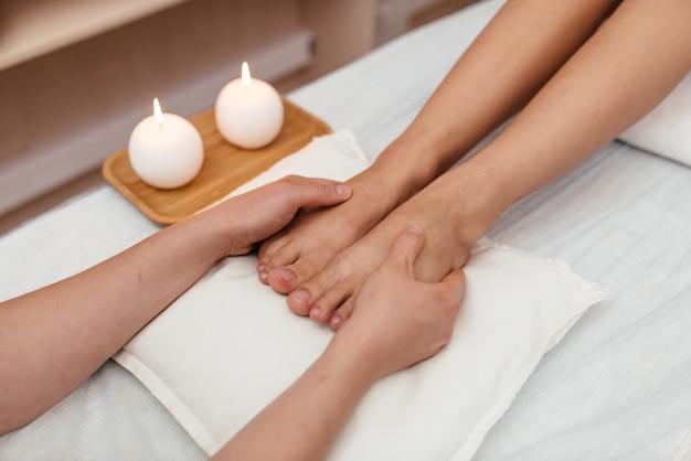 Chiuda in su dei piedi della donna e delle decorazioni del salone di bellezza. estetista che fa massaggio ai piedi. concetto di cura del corpo, spa e massaggi.