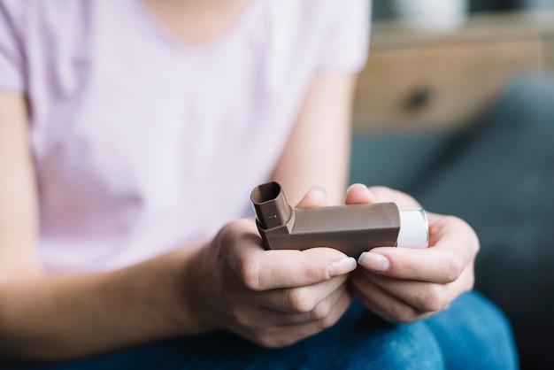 Primo piano della mano di una donna che tiene l'inalatore per l'asma Foto Premium
