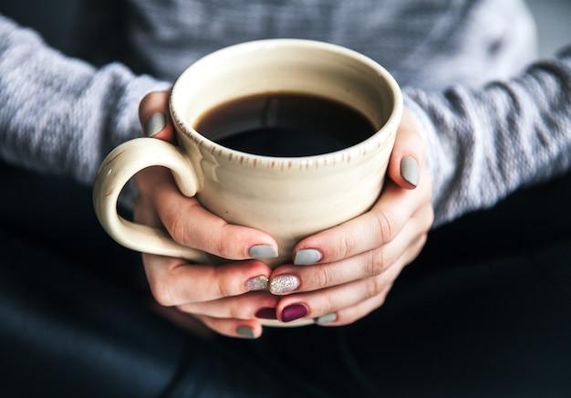 Primo piano della mano di una donna che tiene una tazza di caffè caldo. moda, tempo libero