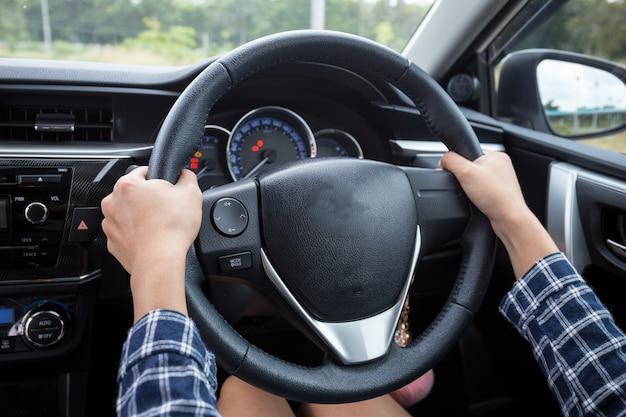 Primo piano del volante della tenuta della mano della donna per l'autista di automobile