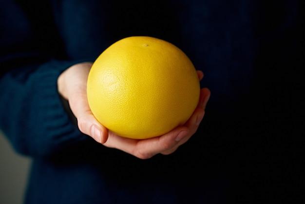 Primo piano della mano della donna che tiene il pompelmo di agrumi luminoso giallo bianco intero su oscurità