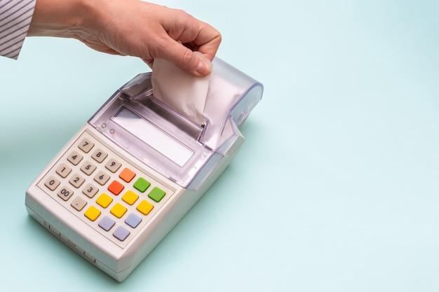 Primo piano della mano di una donna che strappa un assegno da un registratore di cassa su un blu