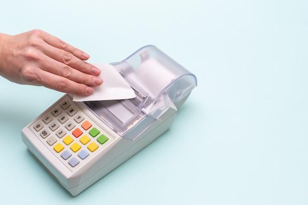 Primo piano della mano di una donna che strappa un assegno da un vecchio registratore di cassa