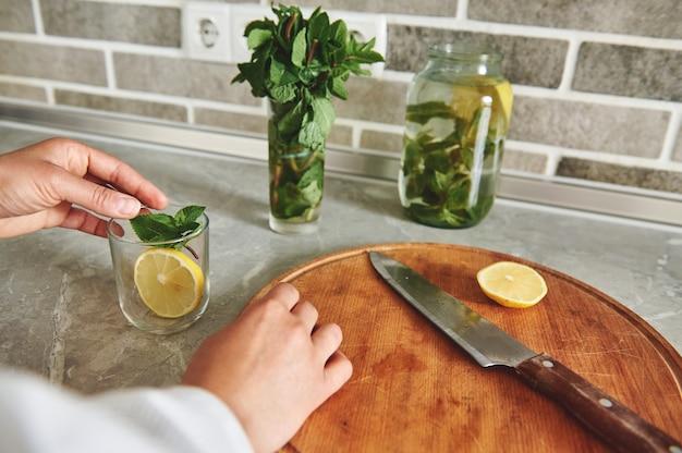 Primo piano della mano di una donna che lancia una fetta di limone e foglie di menta in un bicchiere trasparente.