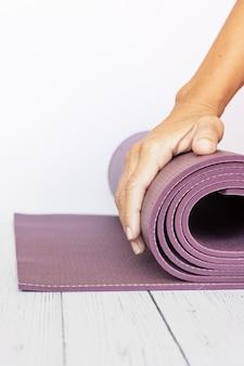 Primo piano della mano di una donna che spiega una stuoia di yoga viola su legno bianco