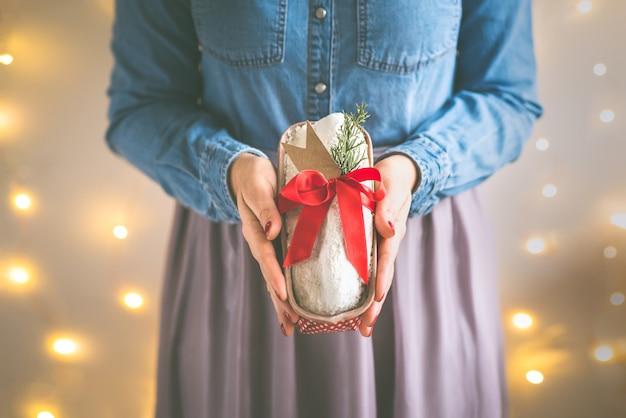Chiuda su delle mani della donna che tengono il dolce stollen casalingo di natale avvolto come regalo. messa a fuoco selettiva.