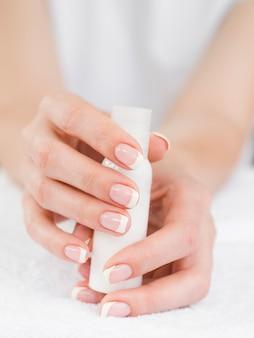 Chiuda sulle mani della donna che tengono il dispositivo di rimozione dello smalto
