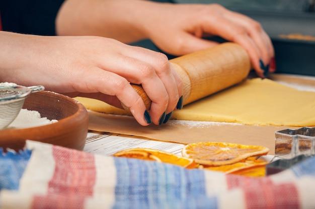 Chiuda in su delle mani della donna che preparano la pasta per i biscotti