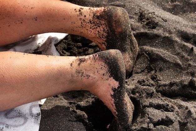 Primo piano delle gambe e dei piedi di una donna nella sabbia, sdraiato sulla sabbia nera vulcanica sulla spiaggia.tenerife