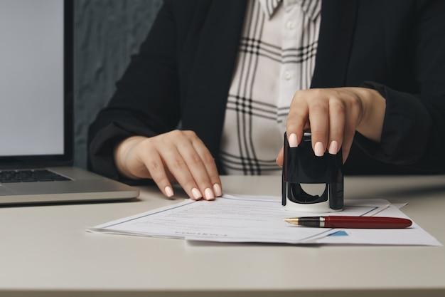 Primo piano sulla mano notaio della donna che timbra il documento. notaio concetto pubblico.