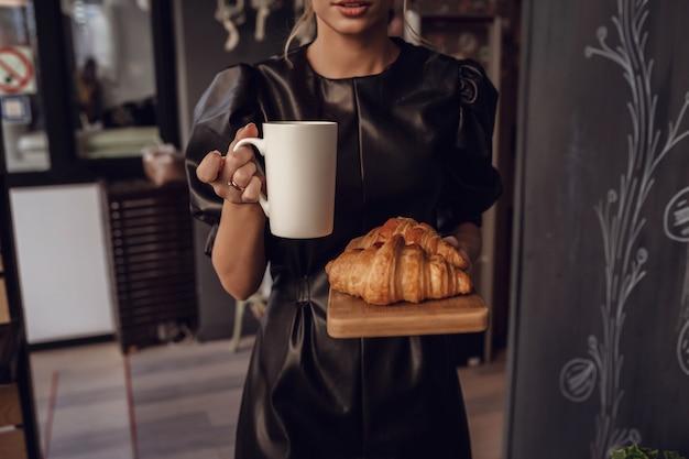 Chiuda sulla donna che serve caffè caldo in tazza bianca e croissant sul piatto di legno nella caffetteria
